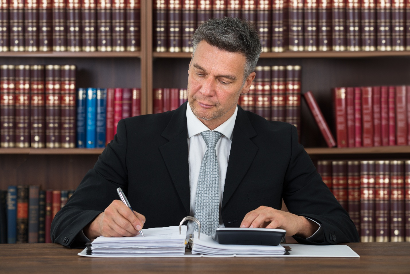 man in library writing on notebook