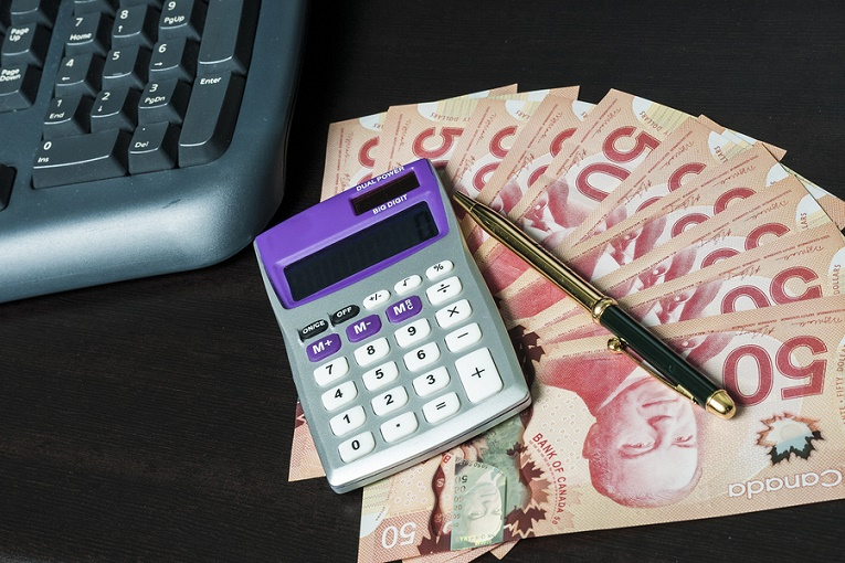 pen, calculator on top of Canadian pink 50 dollar bills next to keyboard