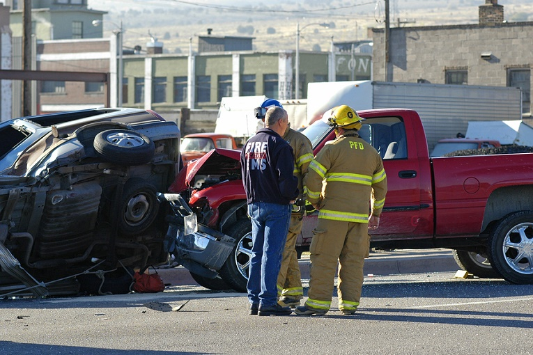 """firemen in front of vehicle crash with red pickup truck"""