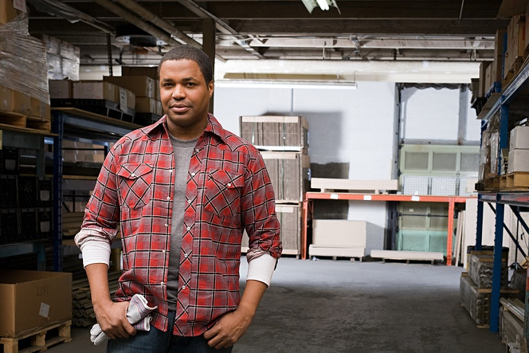 """""""man in flannel shirt standing in warehouse staring"""""""