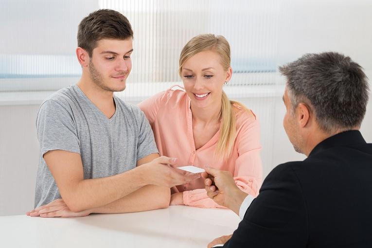 """""""man handing couple a business card"""""""