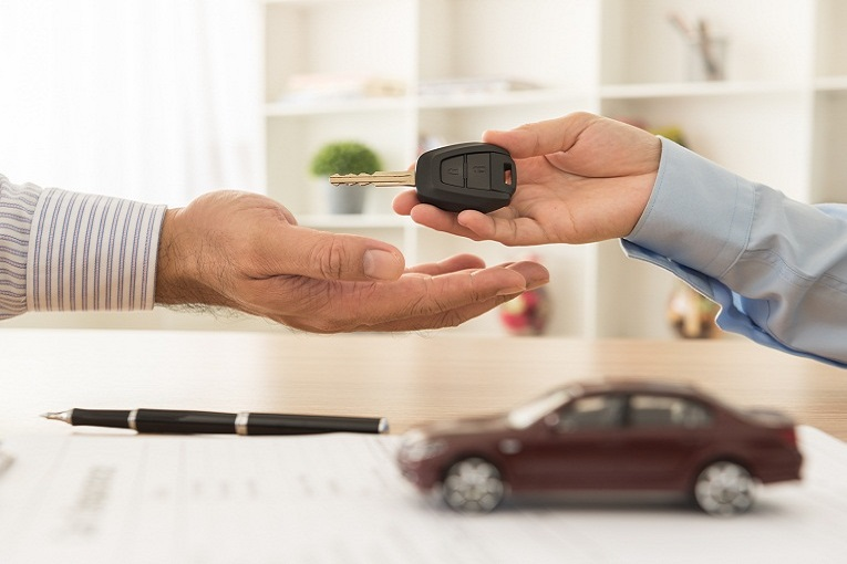 """hand handing over car key to another hand"""