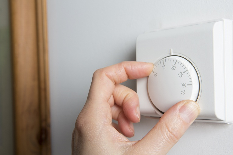 """hand lowering heat on thermostat"""