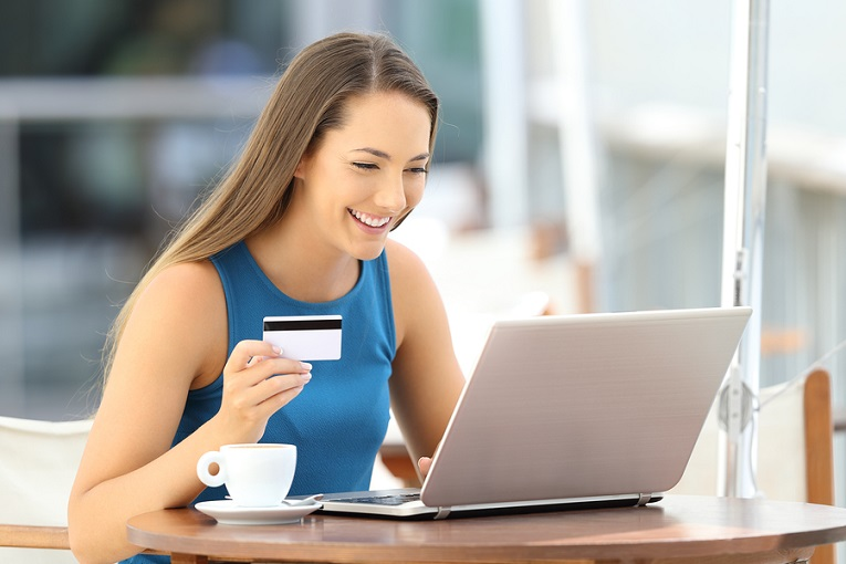 """""""woman holding credit card while smiling and looking at laptop"""""""