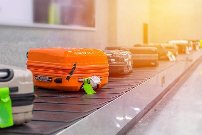 """""""orange luggage suitcase on conveyor belt"""""""