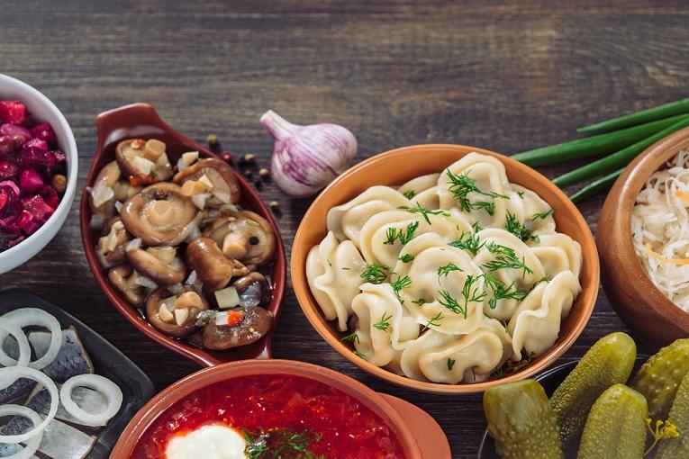 """bowls of food mushrooms pierogies borsch soup pickles"""