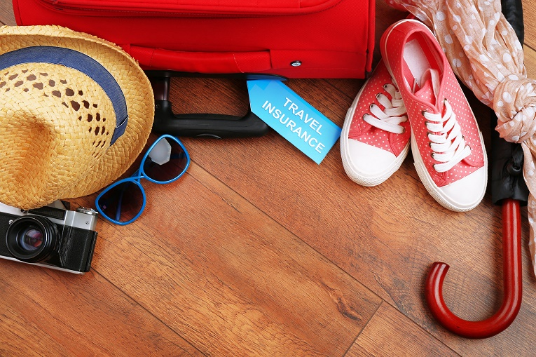 Travel insurance tag with luggage, hats, sungalsses, red polka dot shoes and umbrella on wood floors