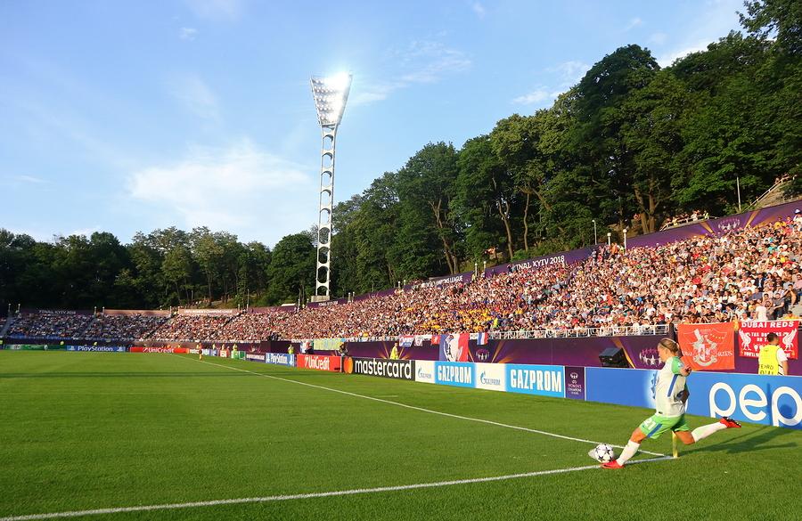 Women playing soccer in big field