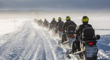men riding snowmobiles