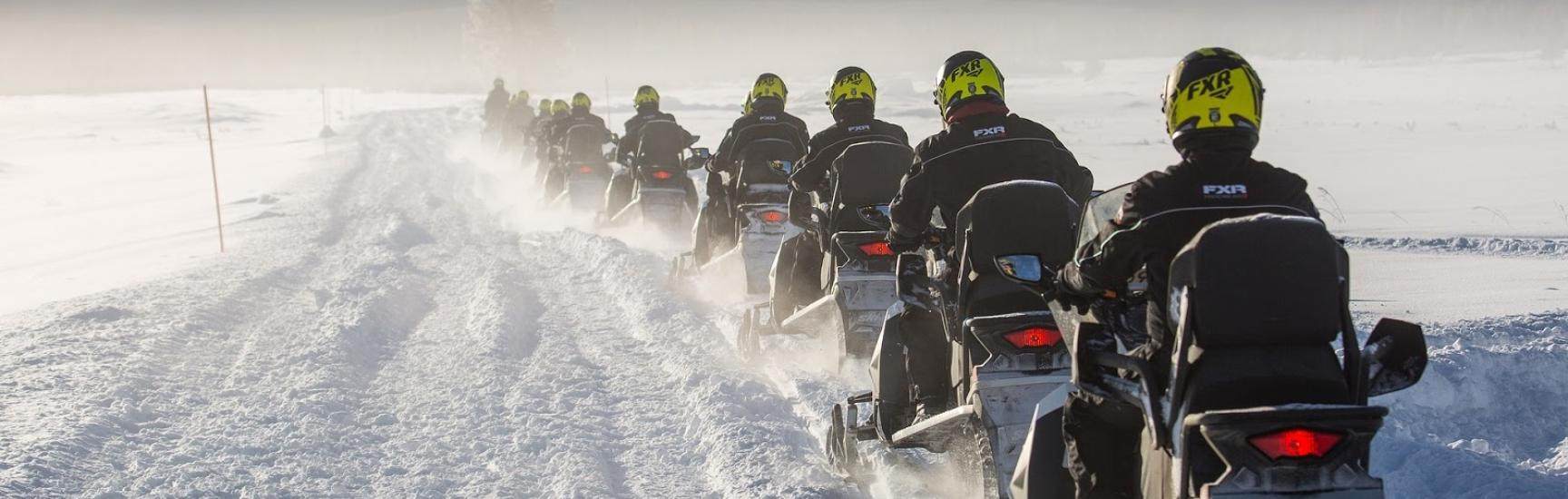 men riding snowmobiles