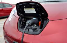 red electric car with charger plugged in